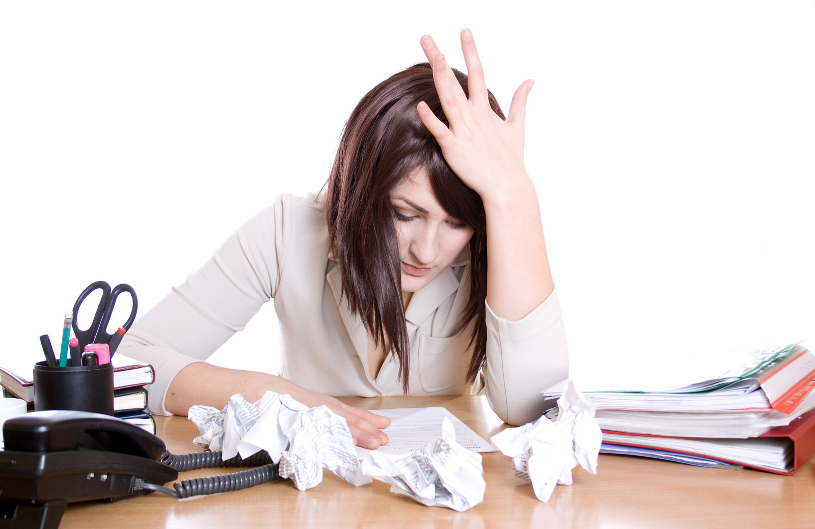 Woman looking stressed with crumpled papers on her desk